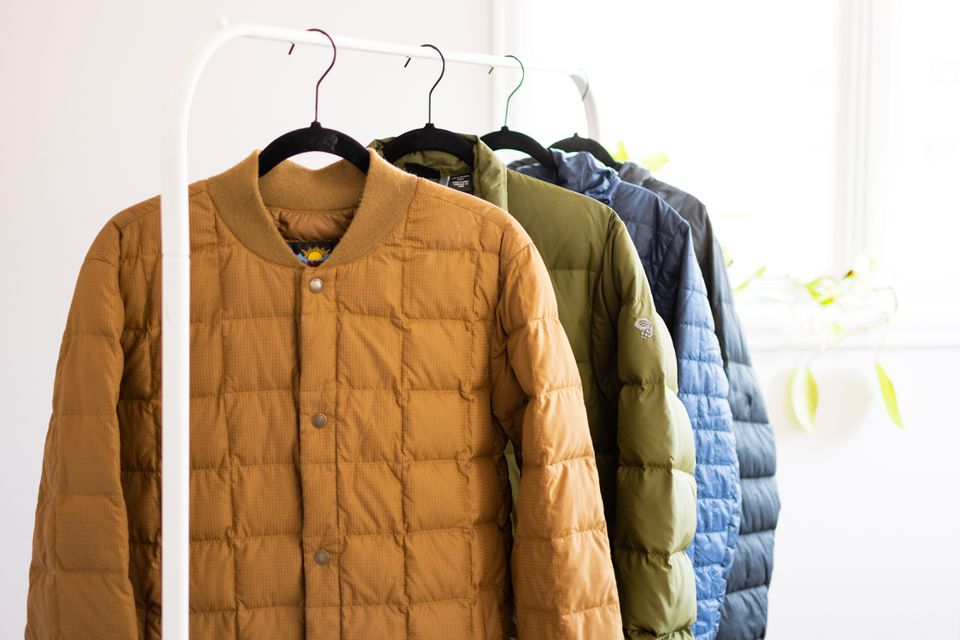 Yellow, green, blue and black down coats hanging on white metal hanger