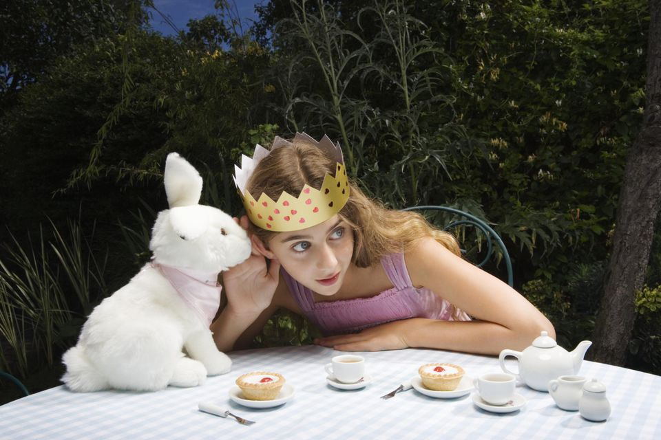 Girl wearing a paper crown having a tea party