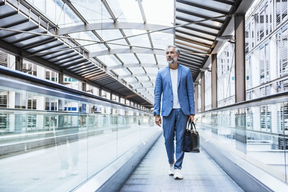 Businessman walking on moving walkway