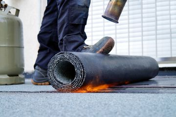 Flat roof installation with propane blowtorch during construction works with roofing felt. Heating and melting bitumen roofing felt.