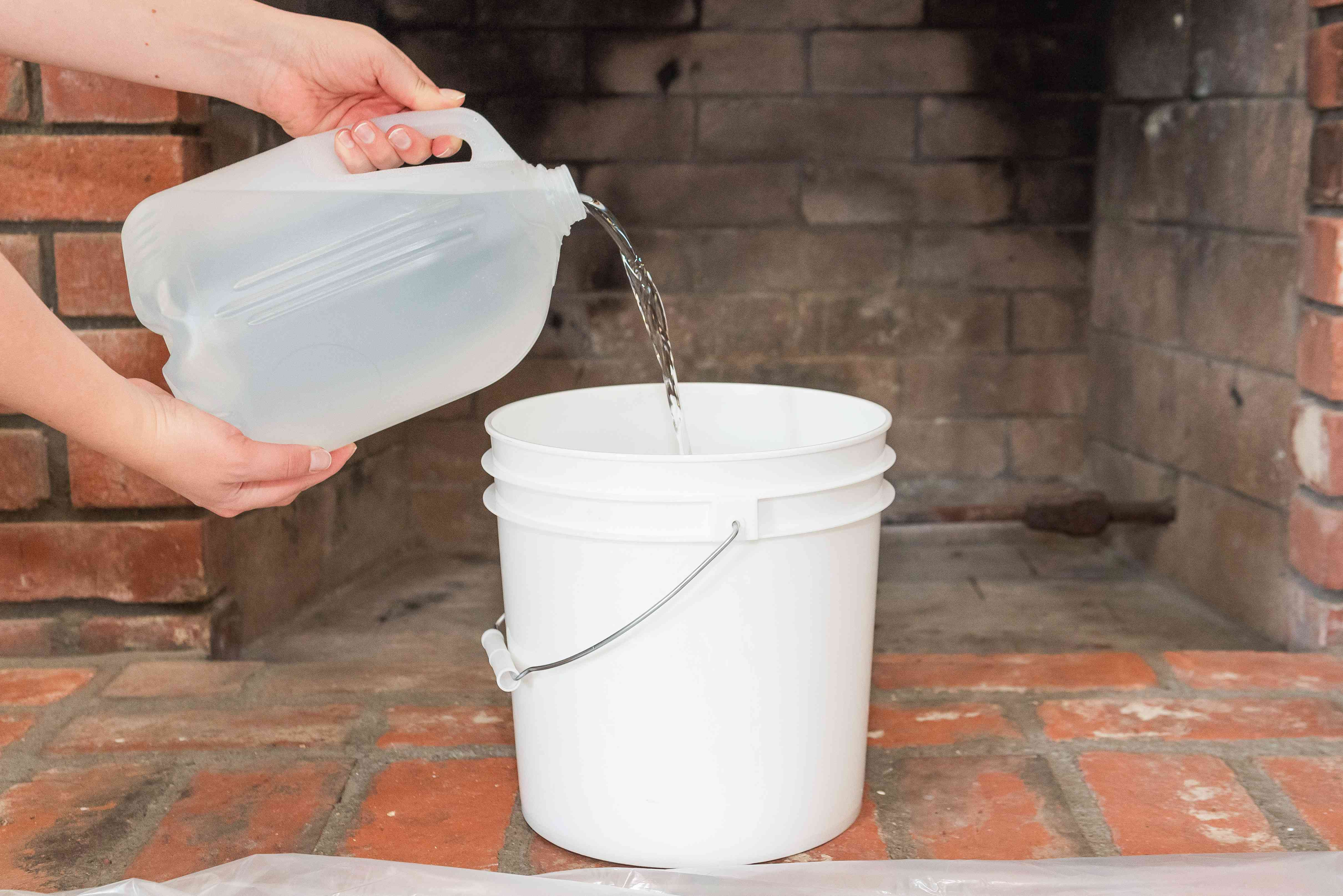 Gallon of warm water poured into white bucket in front of fireplace