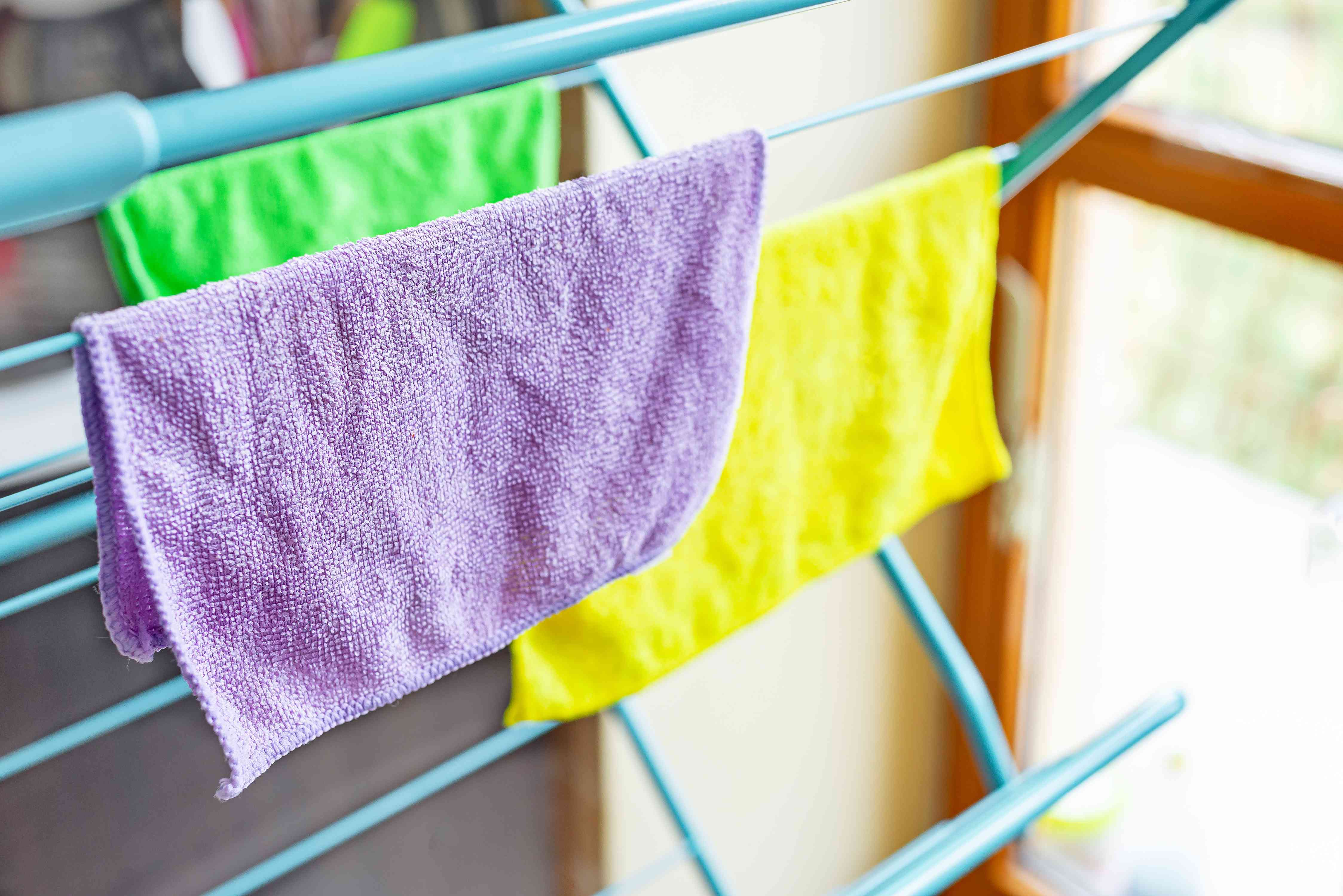 Multi-colored microfiber cloths hanging on drying rack to air dry