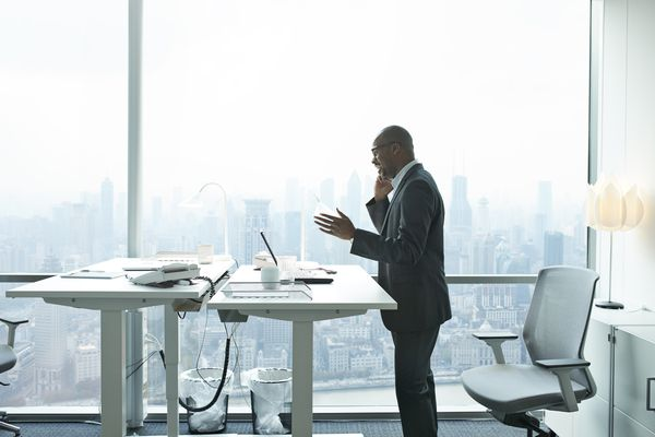 Businessman on the phone standing near a work desk overlooking a cityscape.