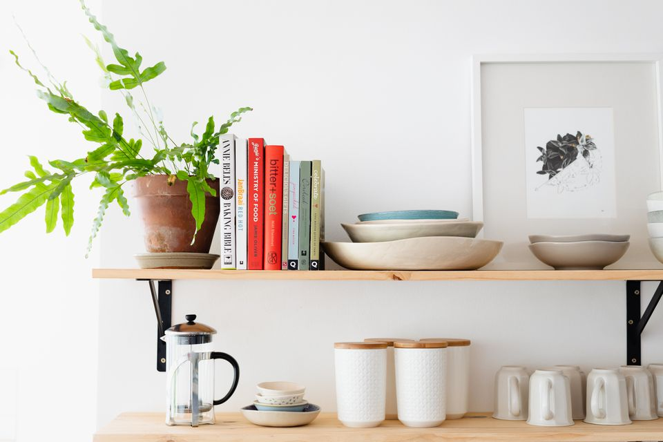 Wooden shelves displaying cookbooks and houseplant next to kitchenware and coffee maker