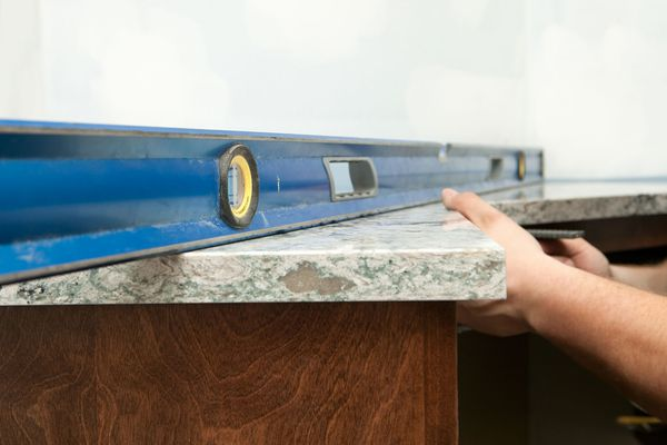 Worker Using a Level to Install Solid Surface Countertop