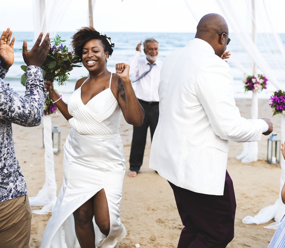 Couple dancing on beach during reception