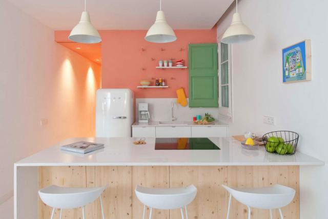 Encimeras blancas con una pared decorativa de color salmón en una cocina blanca