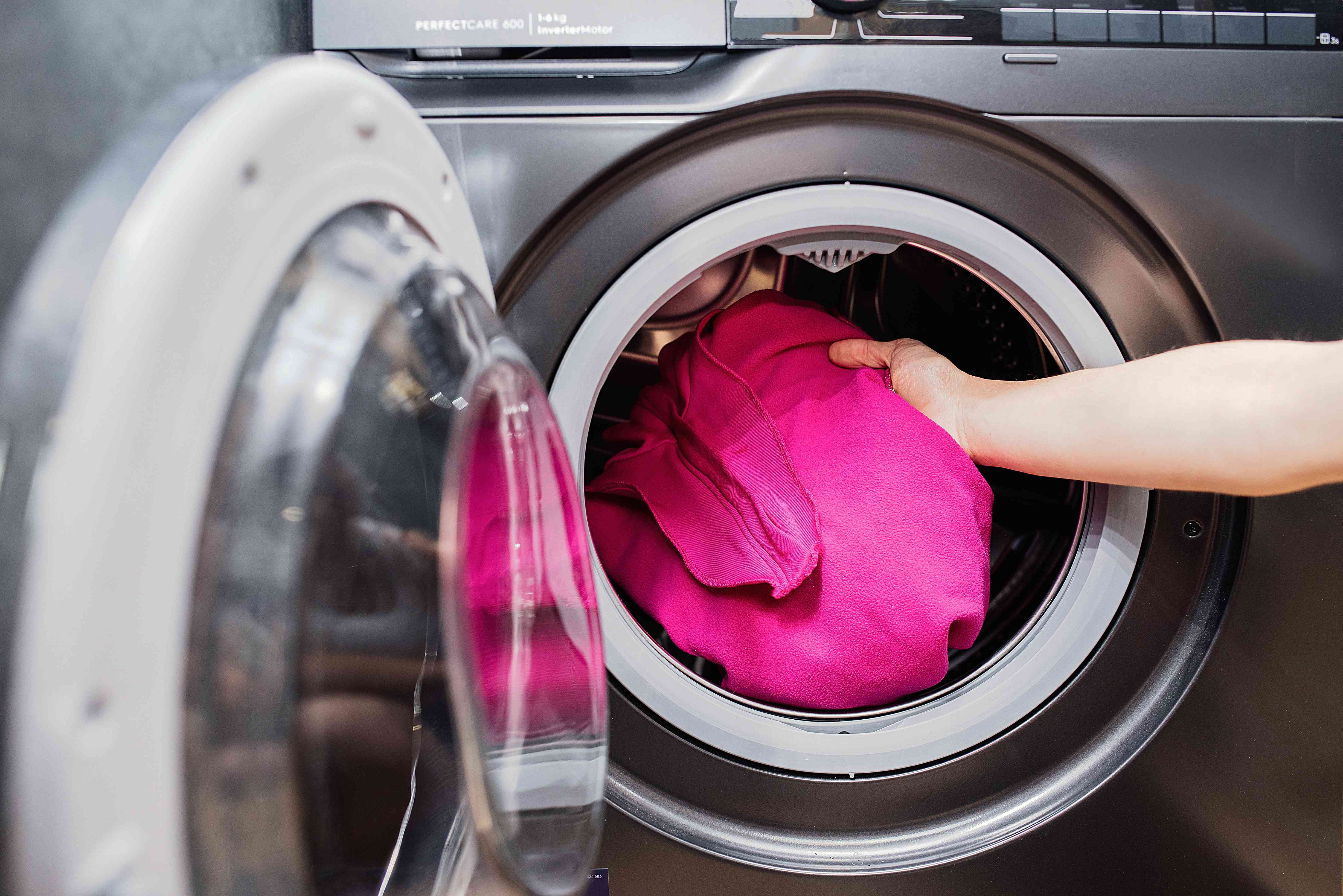 Pink fleece jacket placed in front-loading washing machine