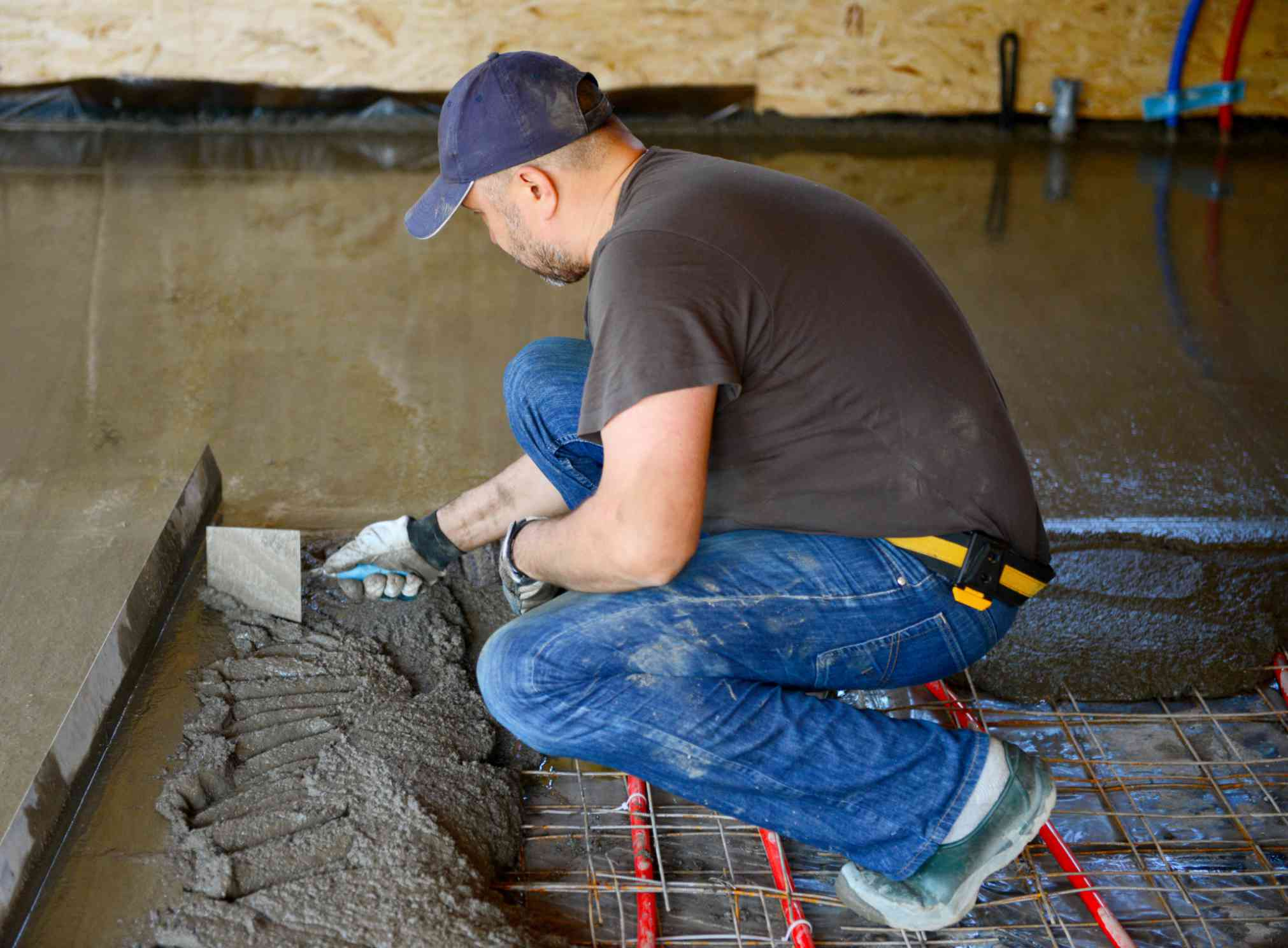 Worker installing plumbing in concrete slab