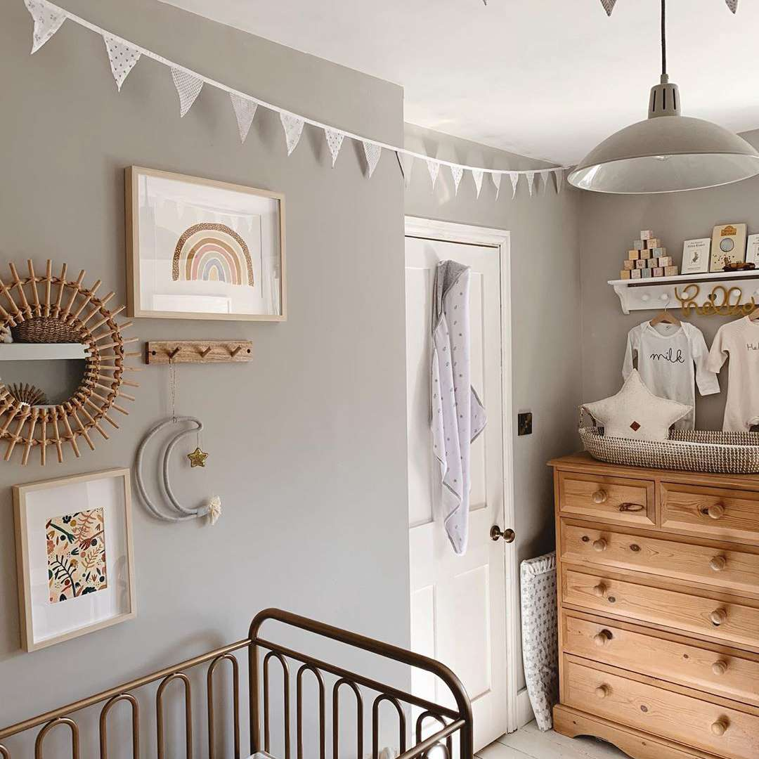 Neutral nursery with gray wall, gold accents, and natural woods.