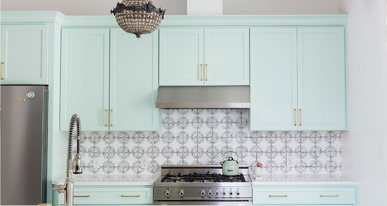 minty green kitchen with brass accents