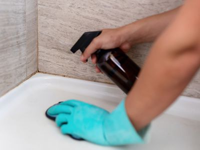 person wiping down grout