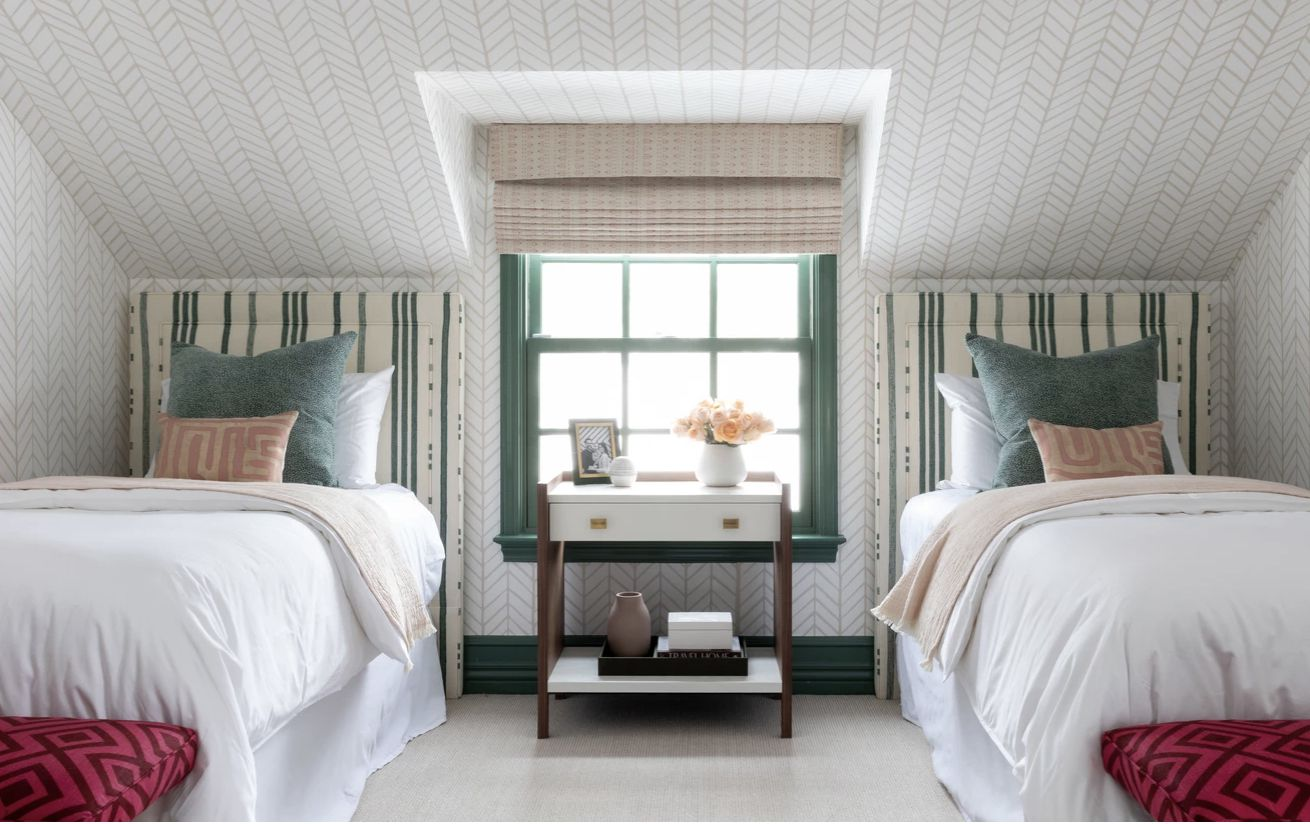 bedroom with mostly green and white colors, red footstools at end of each bed