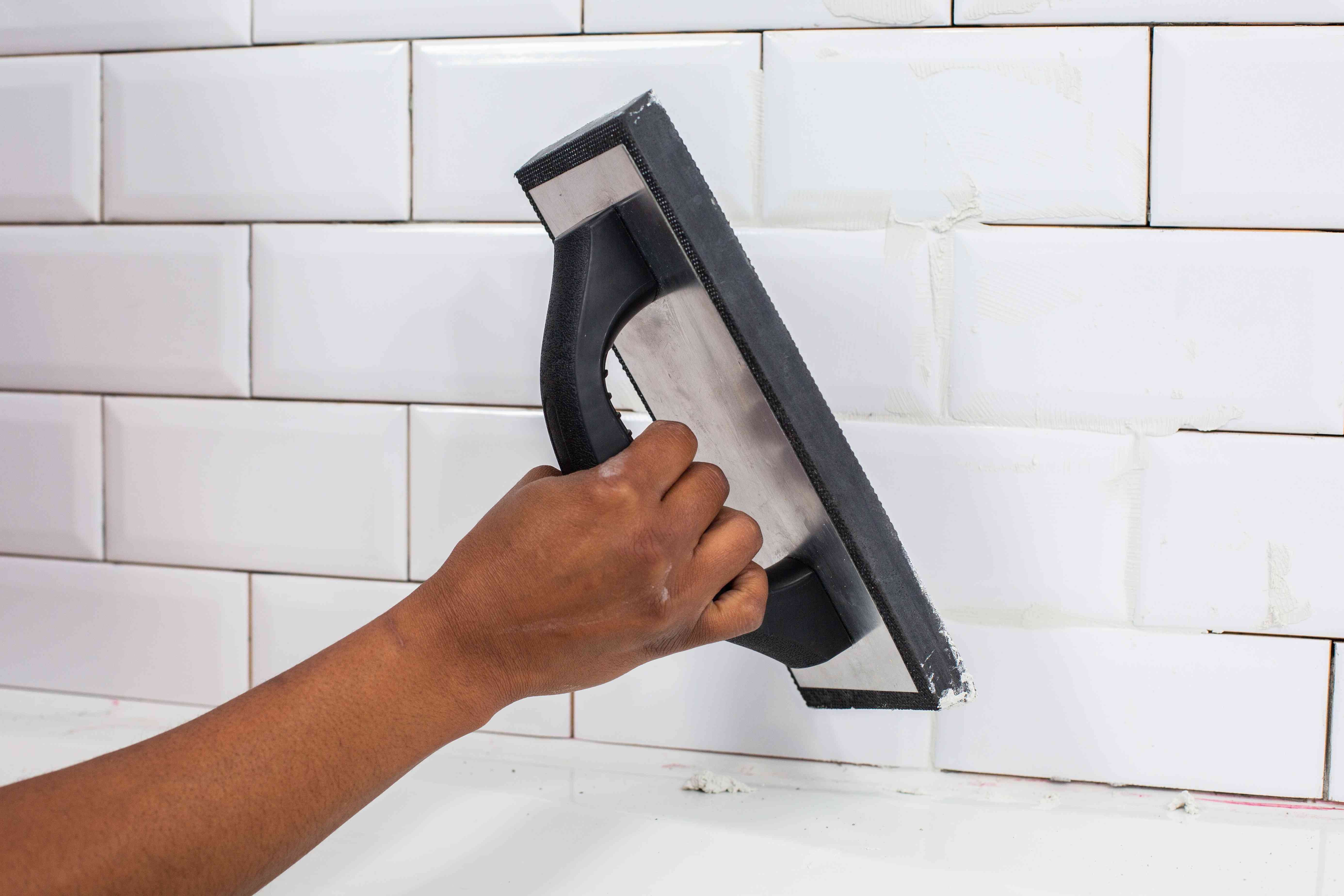Rubber grout float applying grout to white ceramic wall tiles