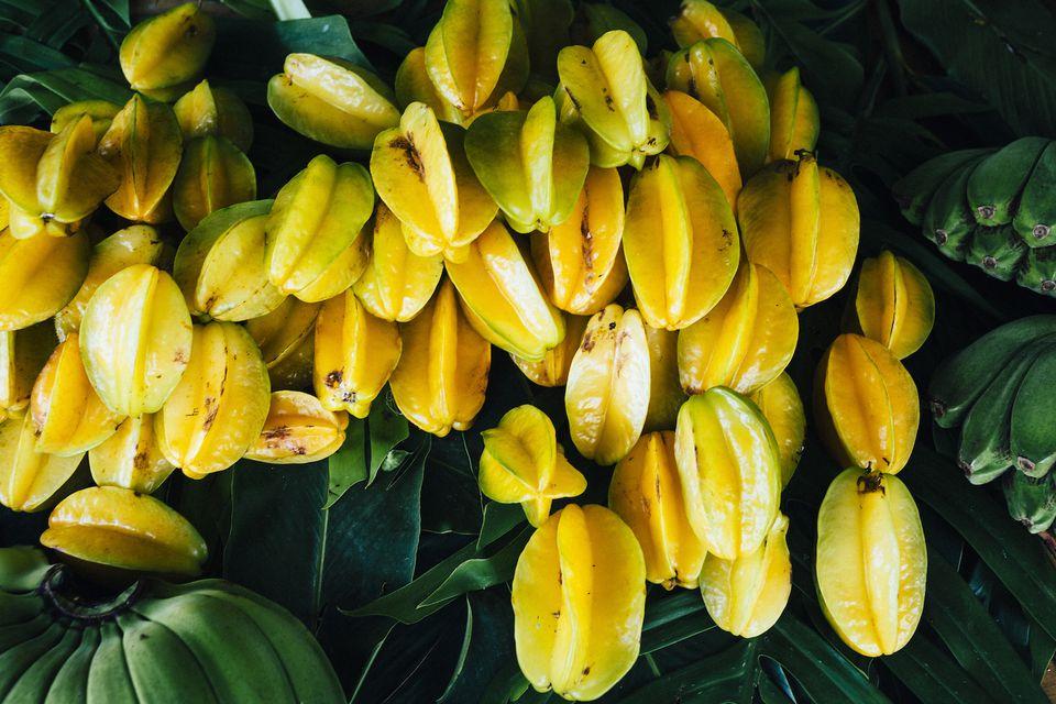 Starfruits ripening to bright yellow, dark green background