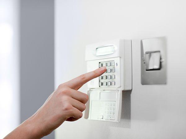 Woman setting burglar alarm
