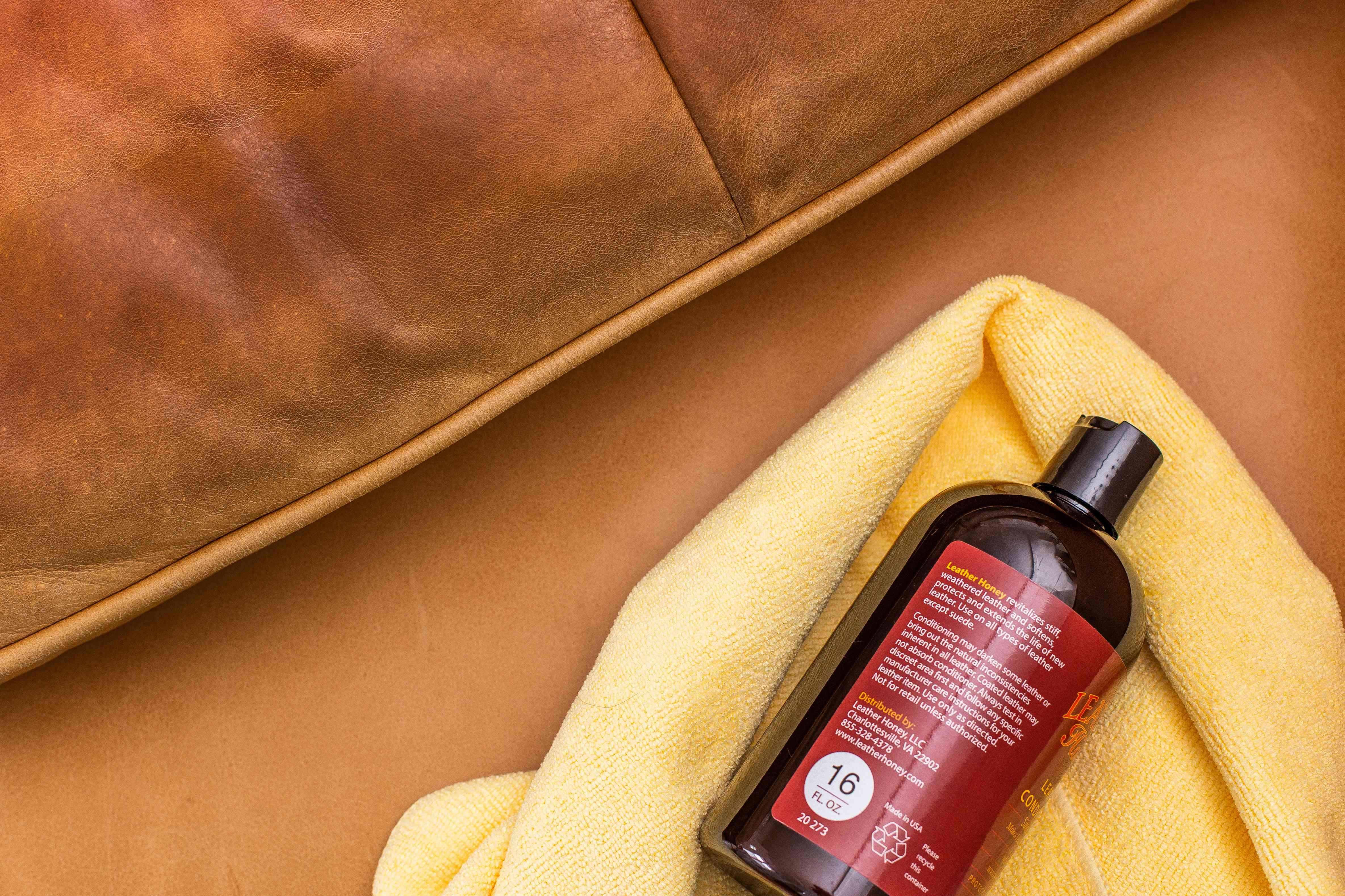 Commercial leather conditioner bottle on yellow microfiber on brown leather couch to restore suppleness