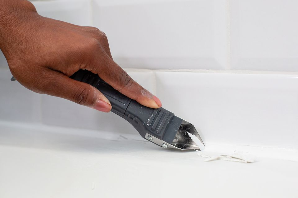 Old caulk being removed with caulk removal scraper