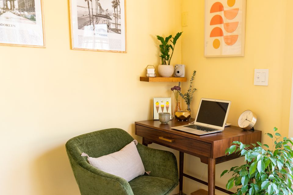 Decorated home office with yellow painted walls, wooden office desk and green chair