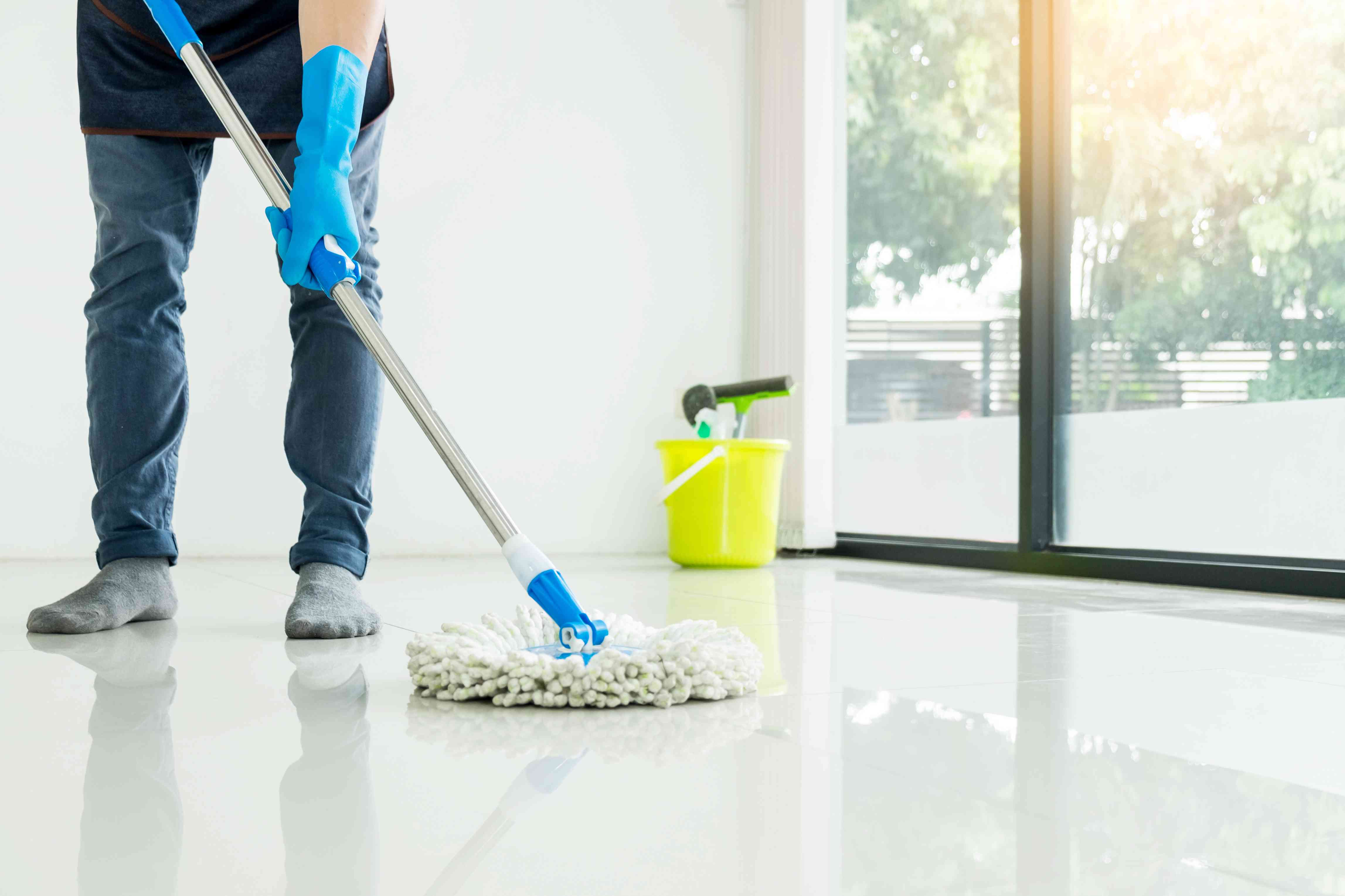 Low Section Man Cleaning Floor With Mop At Home