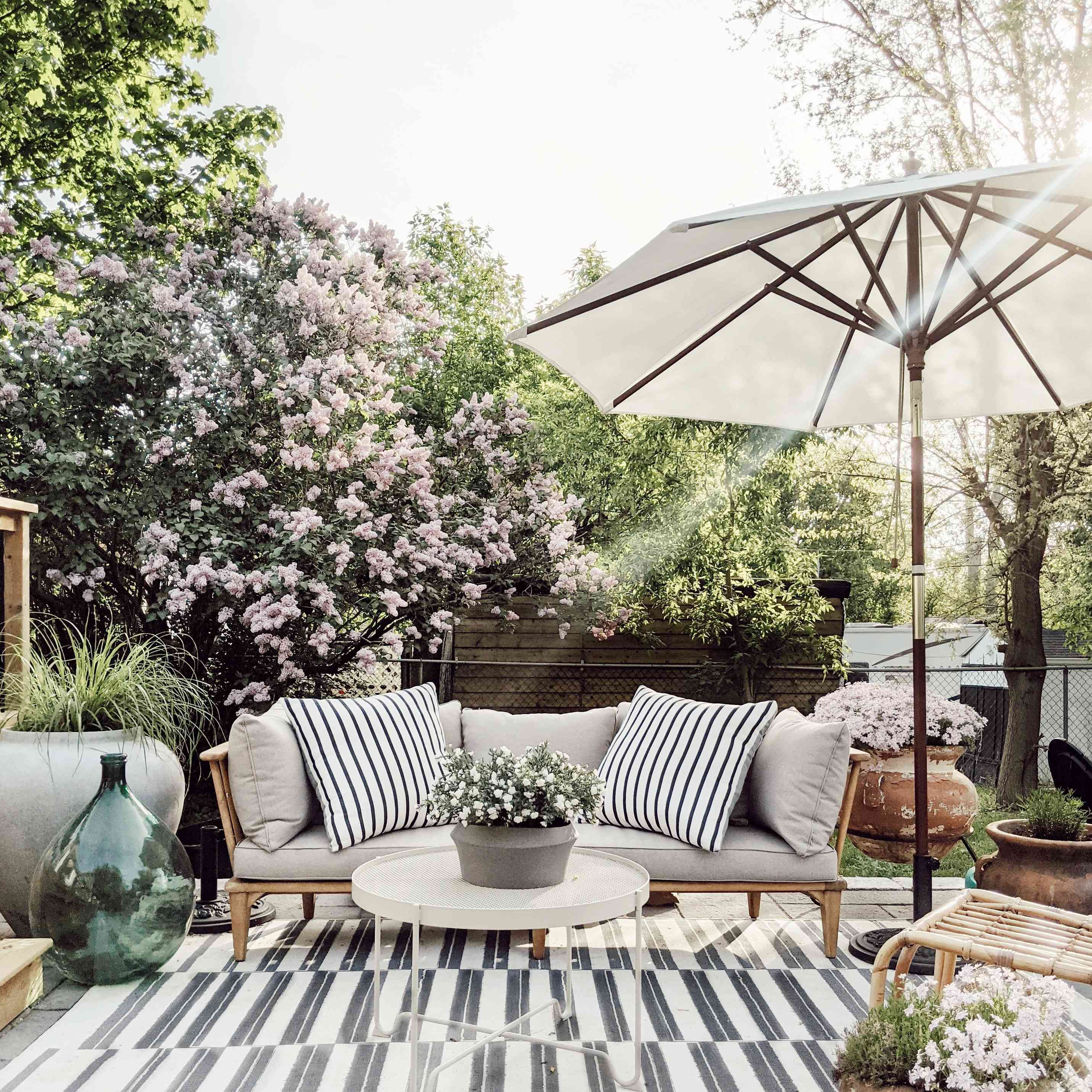 A patio features a striped rug and pilllows with lots of flowers surrounding