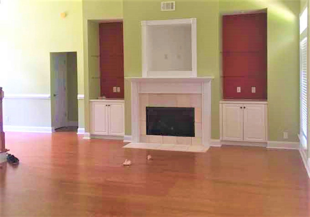 Sala de estar vacía con color mostaza en las paredes, chimenea y muebles empotrados de color rojo