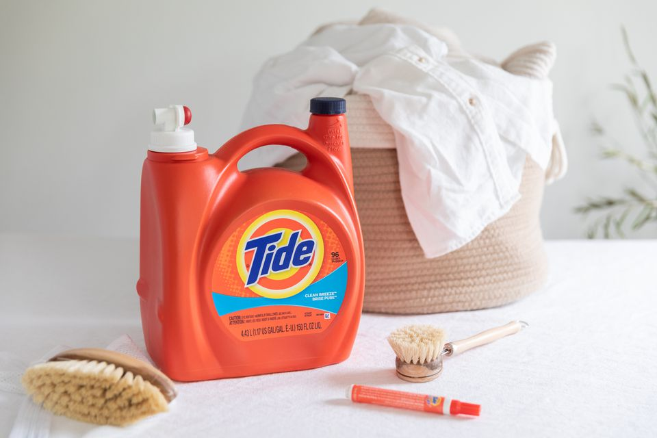 Orange Tide laundry detergent container next to Tide pen, scrubbing brushes and laundry basket