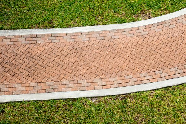 Red brick pattern sidewalk through grass