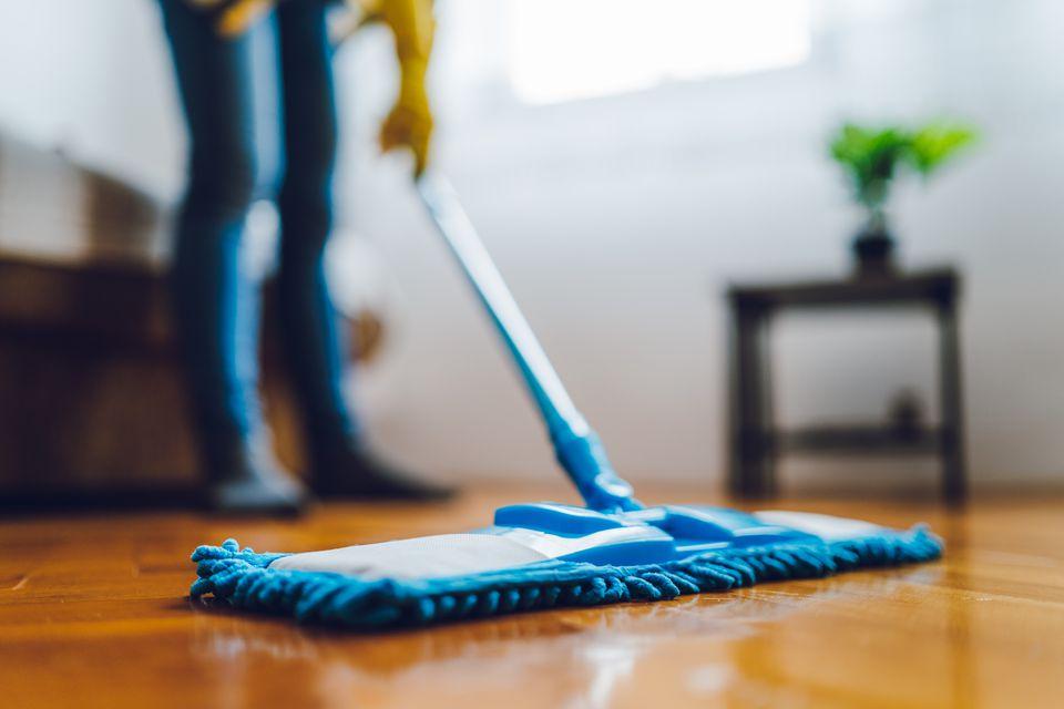 Woman using blue dust mop on hardwood floor