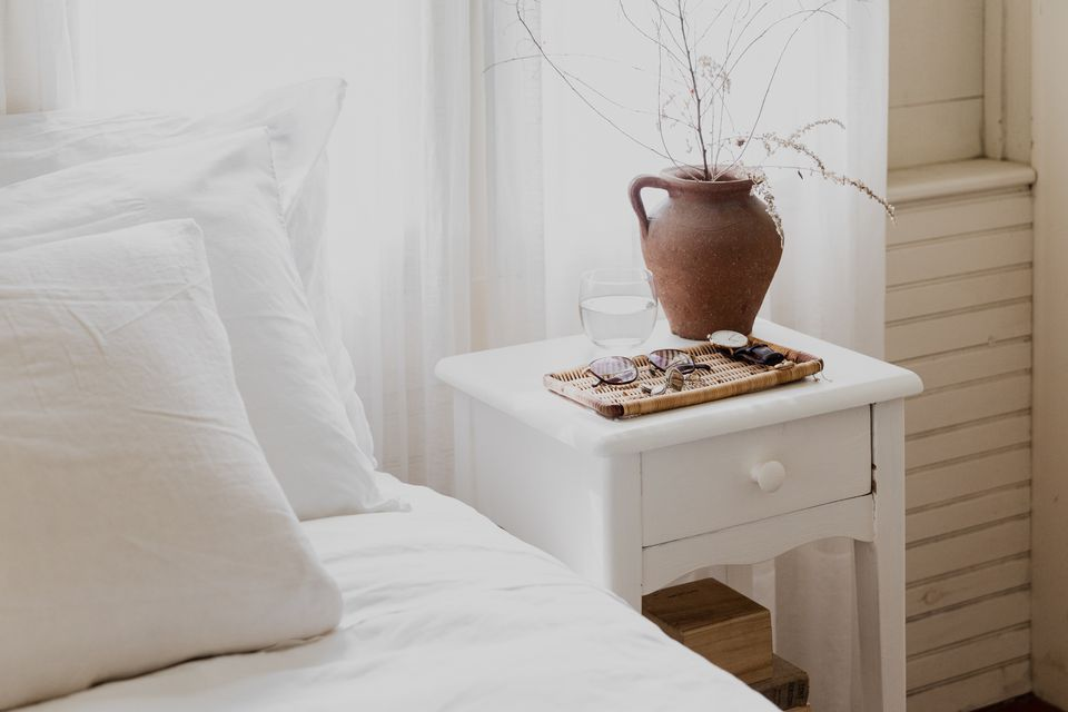 White nightstand with brown clay vase behind wood tray and cup of water