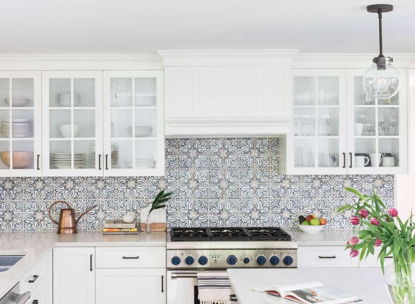 gabinetes blancos con frente de vidrio frente a una placa para salpicaduras de azulejos española