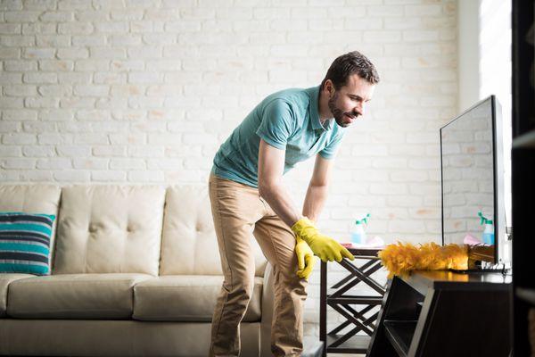 Man dusting TV
