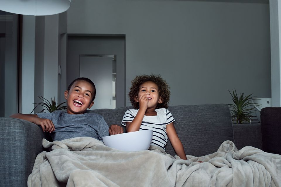 Happy siblings having popcorn while watching TV