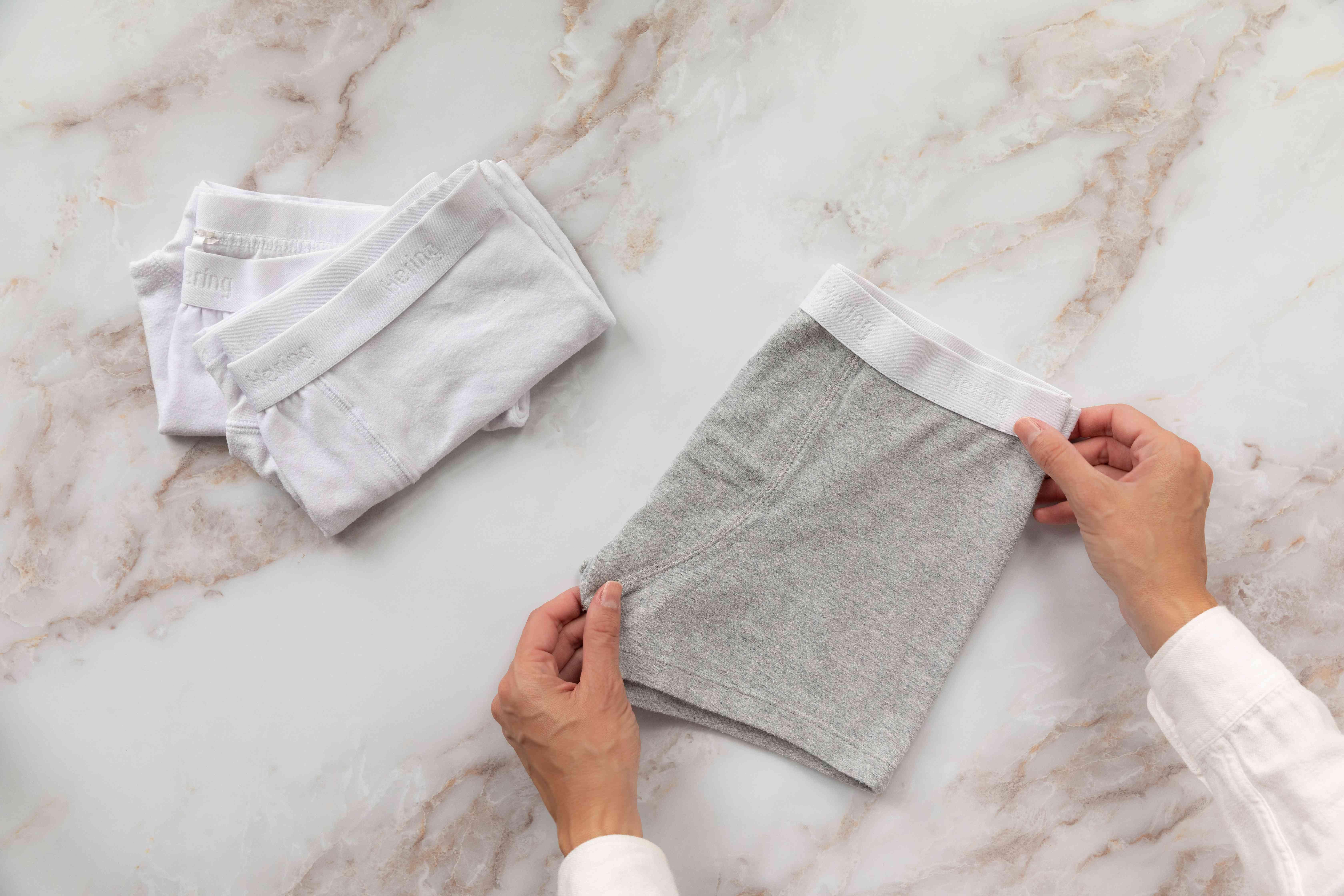 Gray underwear folded vertically in half next to stack of folded white underwear