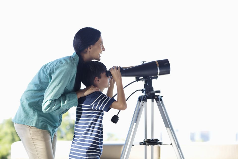 Mother and son using telescope