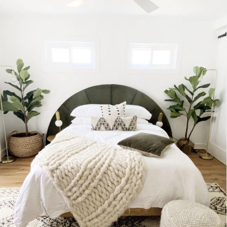 neutral bedroom with plants, chunky woven throw, half circle headboard