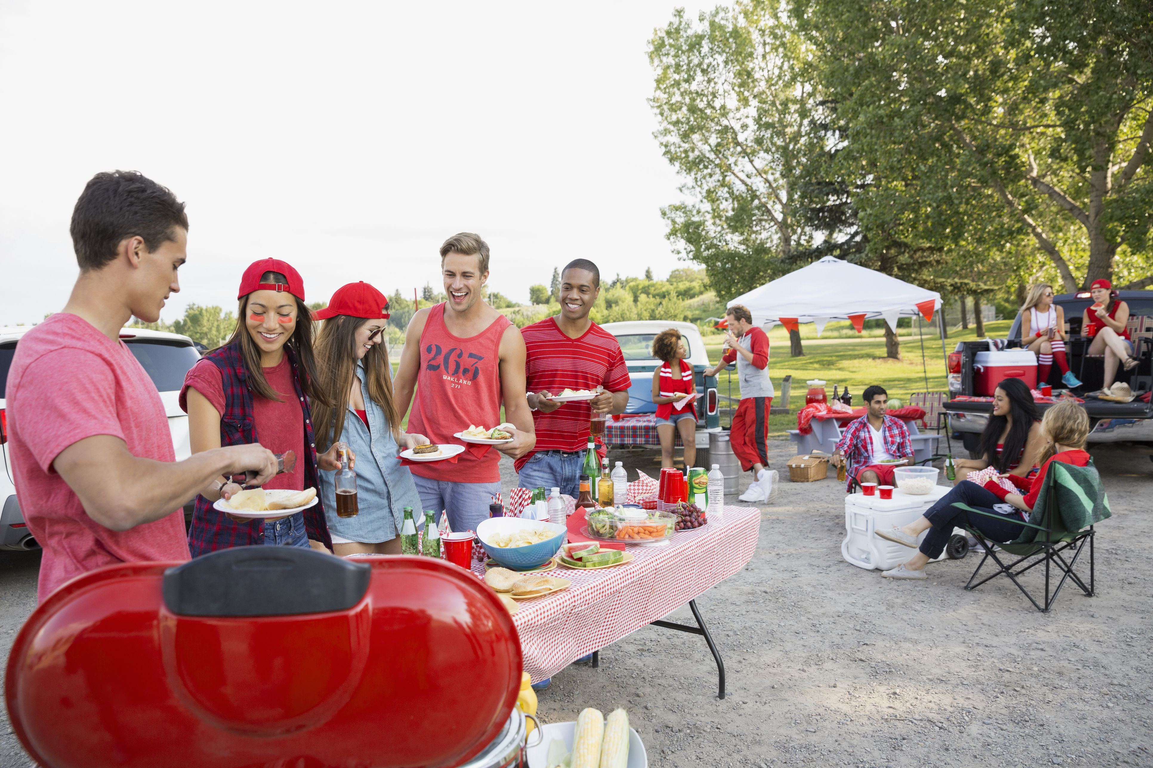 Friends eating at a tailgate barbecue in a field