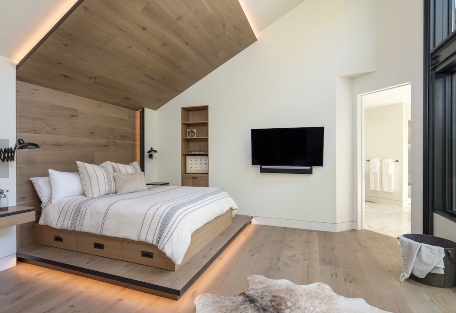 modern bedroom with wooden light accent wall and bed frame, wooden floor, open floorplan