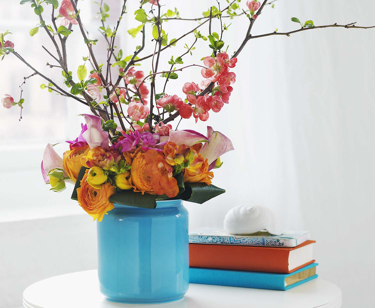 Blue vase on a table with colorful flowers next to three books.
