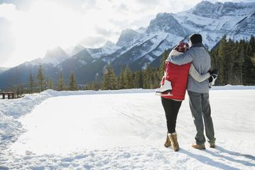 Couple with ice skates hugging below snowy mountain