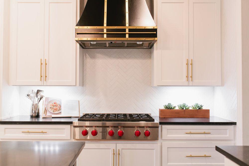 Colorida cocina de campo francesa con pisos de madera oscura y azulejos en las paredes