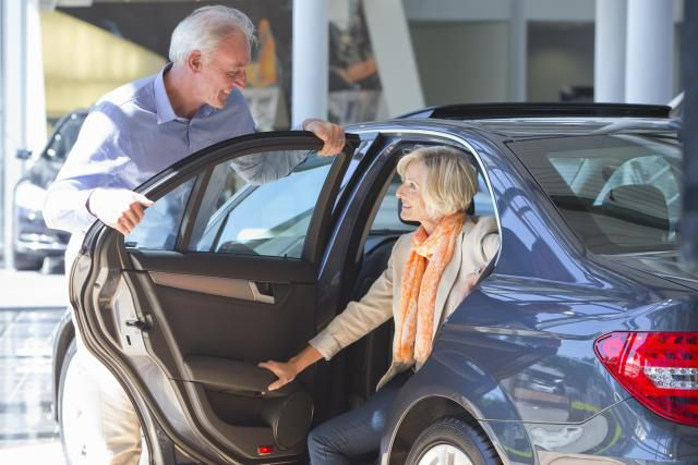 Man holding a car door for a woman