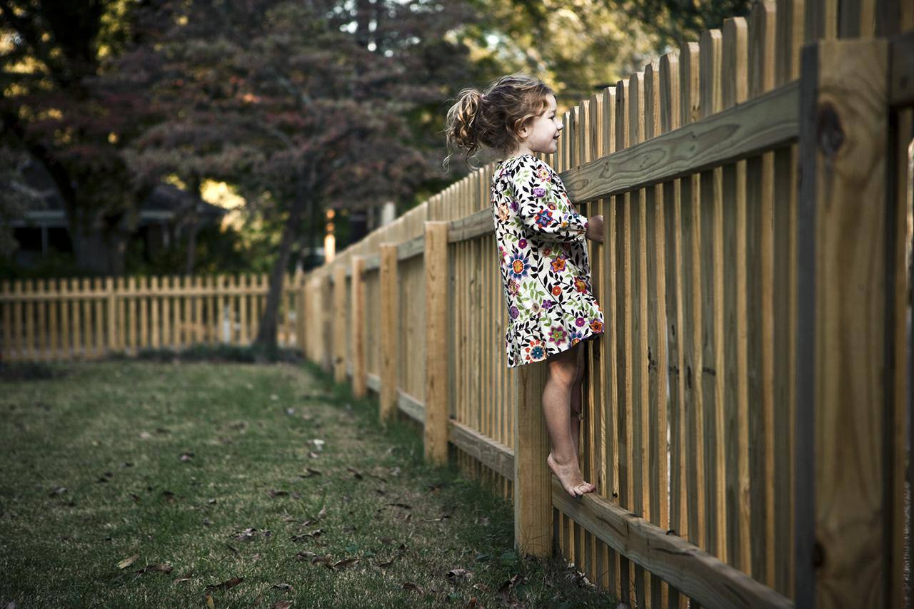 girl (4 yrs) peeking over fence