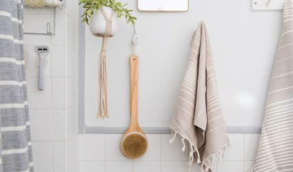 scrub brush and towels hanging on a bathroom wall