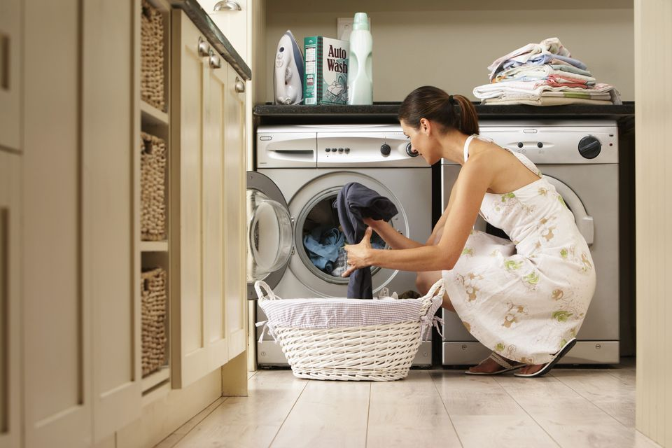 A woman loading a washing machine