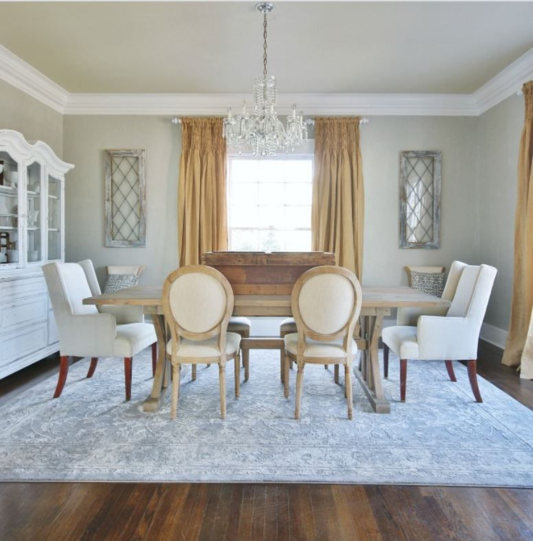 Dining room with beige walls, crown molding, and large crystal chandelier.