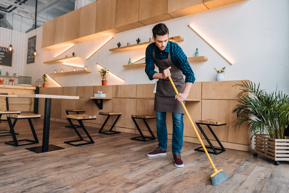 Man sweeping restaurant