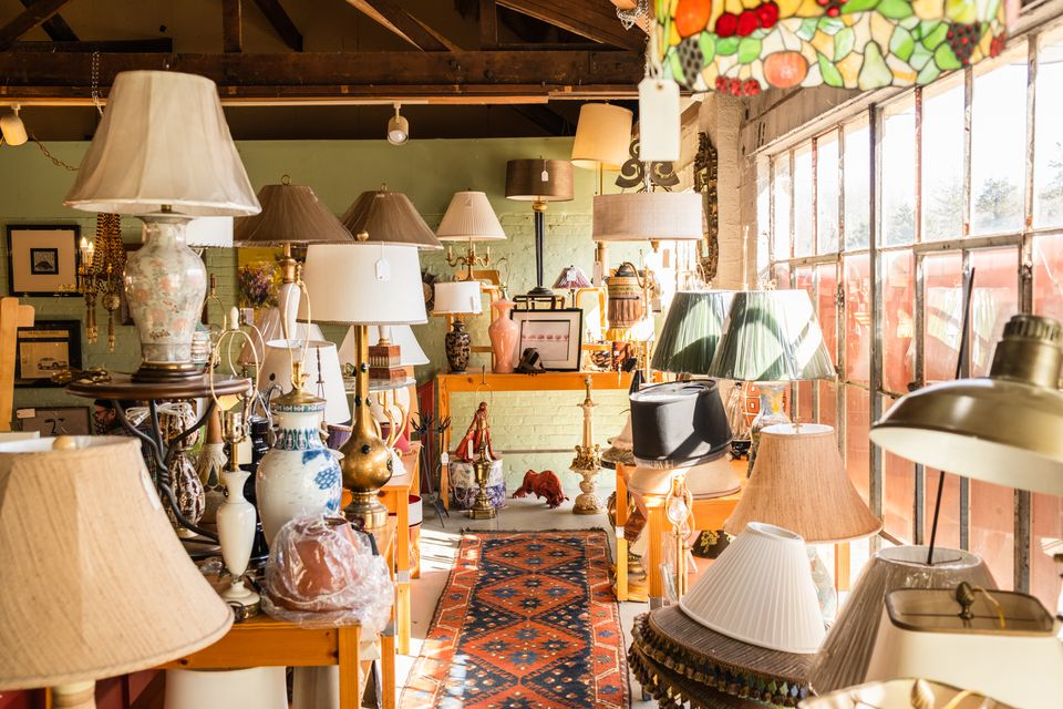 Secondhand decor shop with different lamps and lamp shades next to brightly-lit window