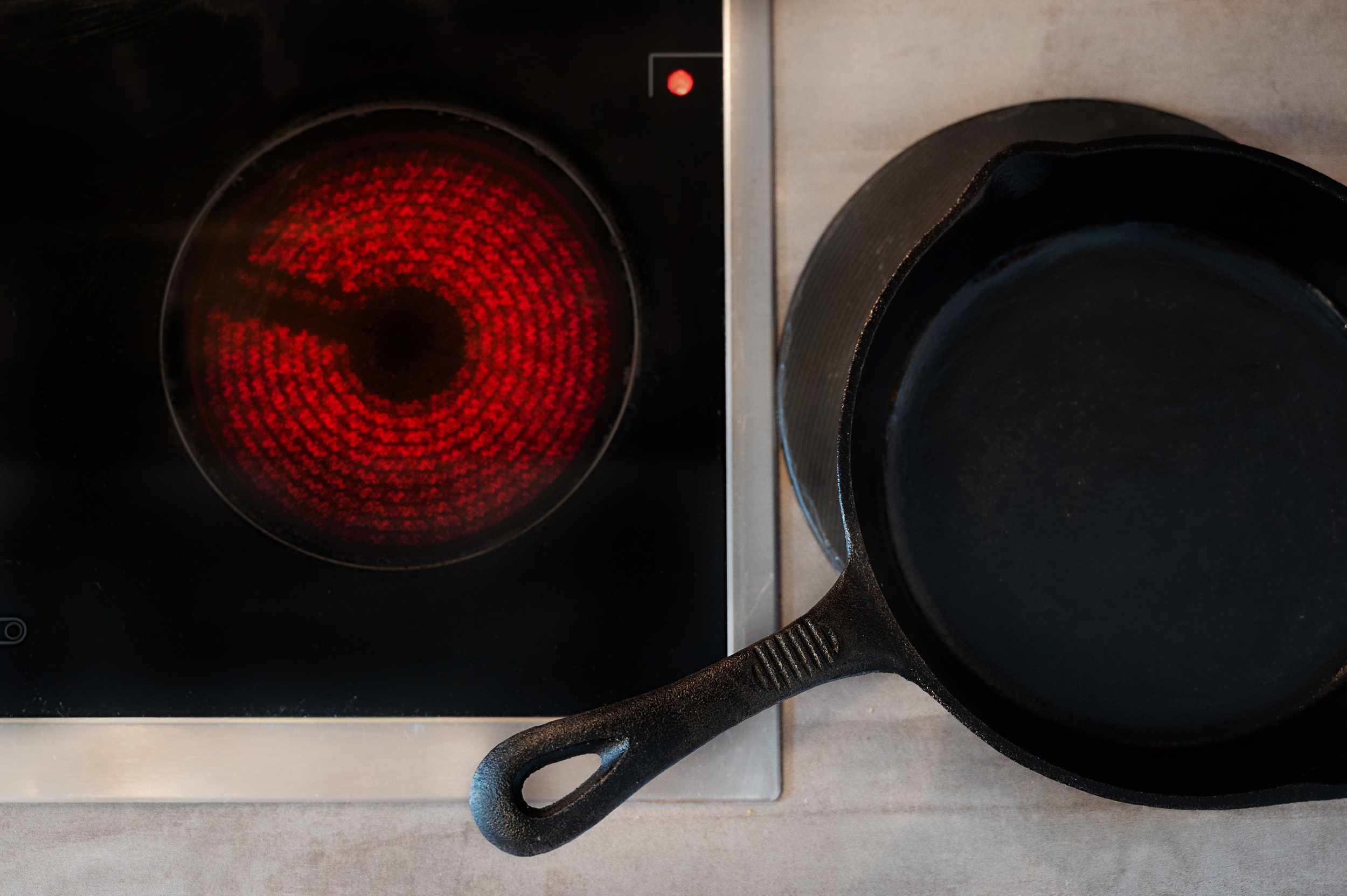 Cast iron griddle pan set on side of hot stove top to cool before cleaning