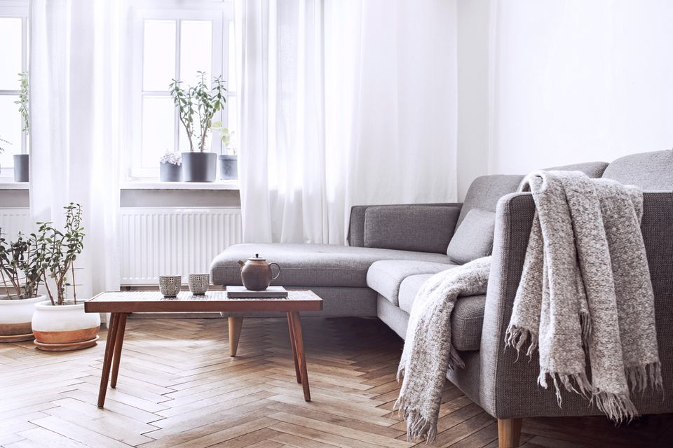 Stylish scandinavian interior of living room with small design table and sofa. White walls, plants on the windowsill. Brown wooden parquet.